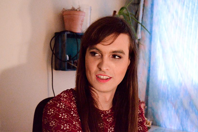 A trans woman with long brown hair, side swept bangs a nose ring. She's wearing a burgundy top. She's shown from the shoulders up.