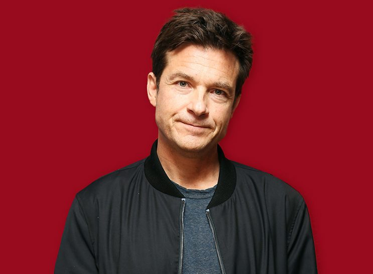 The actor Jason Bateman shown against a red background. He is shown from the shoulders up and is wearing a black vinyl bomber jacket and slate blue shirt.