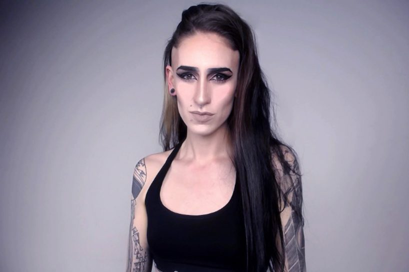 A trans woman shown from the chest up. She is wearing a black tank top and has tattoos on her arms. Her hair is long and dark brown and she's wearing dramatic eye makeup.