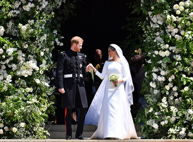 Prince Harry posing next to Meghan Markle outside the chapel at the Royal Wedding