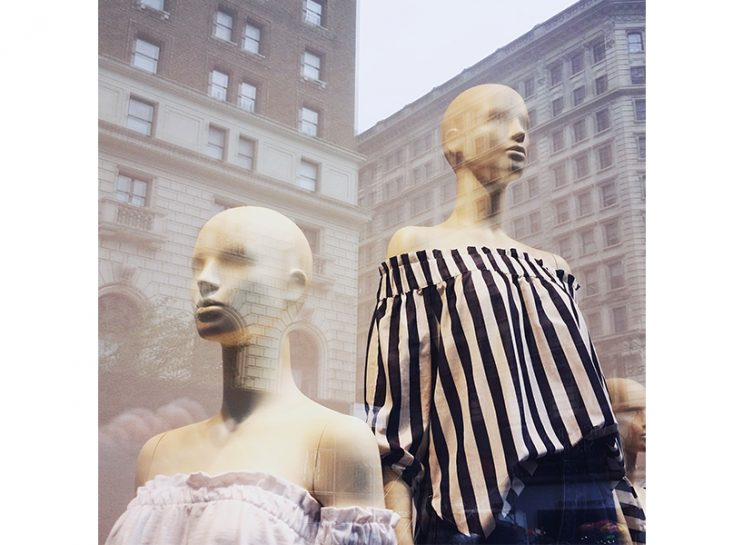 Two mannequins in a retail store window. One is wearing a striped off-the-shoulder top, the other is wearing a lilac version of the same top. You can see the reflection of a building in the window.