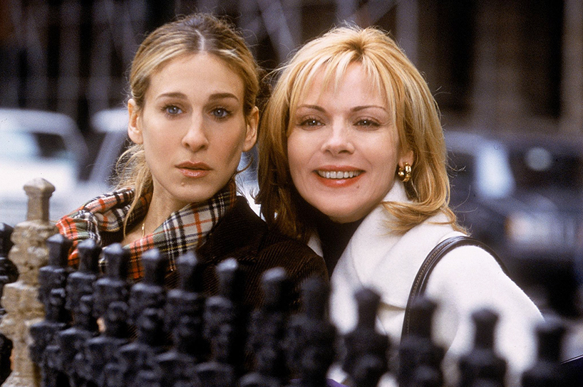 Sarah Jessica Parker and Kim Cattrall look over a fence in a scene from Sex and the City