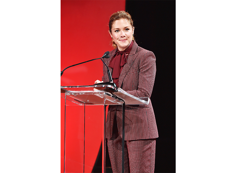 Sophie Grégoire Trudeau stands at a podium, ready to speak, wearing a maroon, checkered suit.