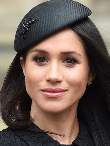 Meghan Markle Monarchy: a photo of Meghan Markle wearing a black hat and smiling with her mouth closed