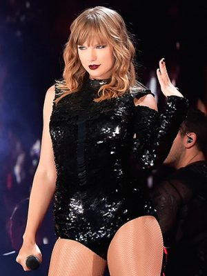 Taylor Swift Kim Kardashian: Taylor Swift poses during a performance wearing a black leotard and looking sassy