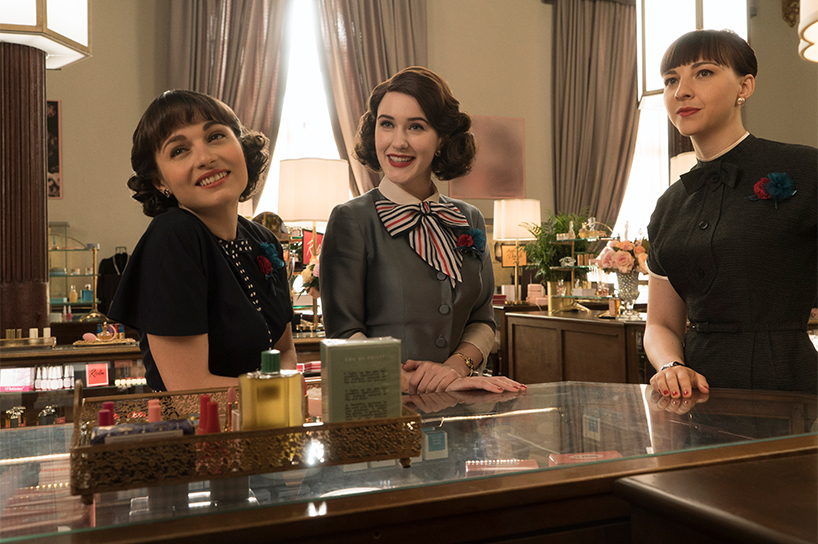 A scene from The Marvellous Mrs. Maisel where three girls are standing and smiling at a cafe counter (Courtesy of Amazon)