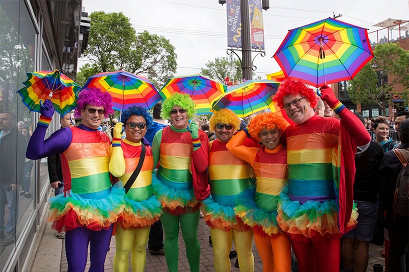 Here is a picture of six pride attendees dressed up in head to toe rainbow gear at Edmonton Pride
