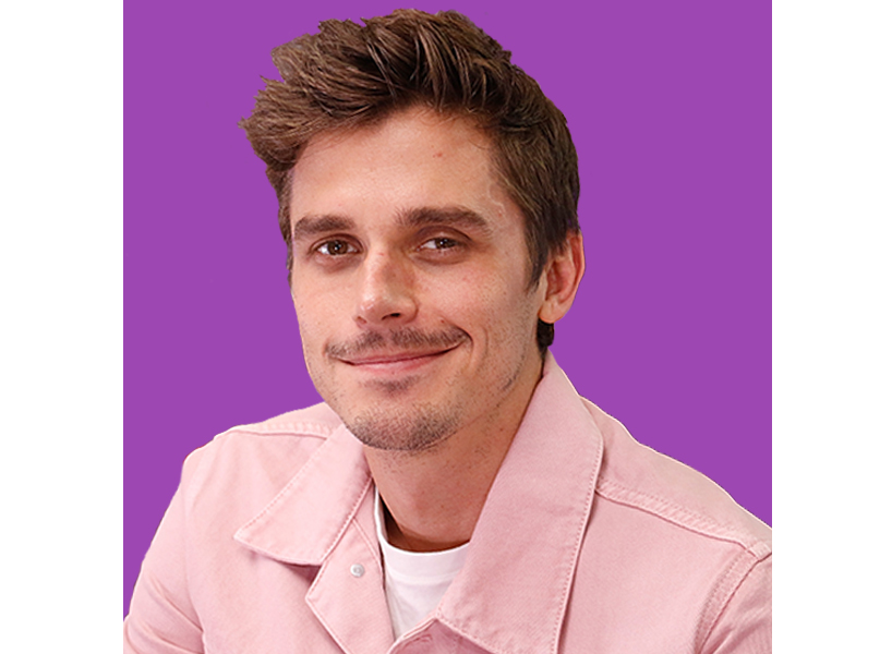 Queer Eye's Antoni smiles at the camera wearing a pink jacket and white t-shirt against a purple background