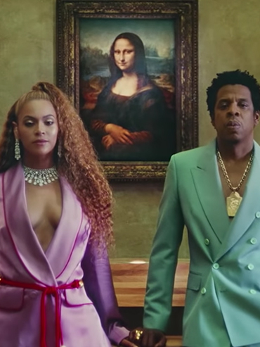 "A screenshot from Beyoncé's video ""Apeshit"" showing Beyoncé and Jay-Z in the Louvre in front of the Mona Lisa"