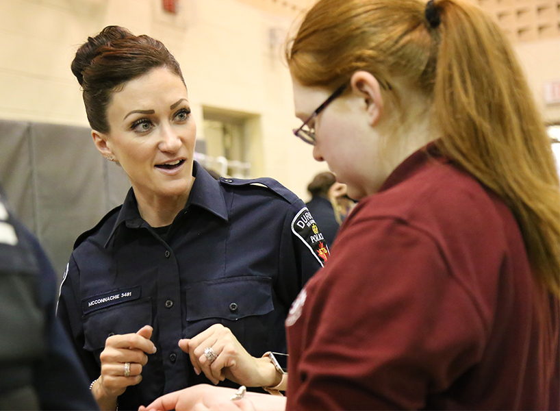 Female police officer talking to red-haired teenage girl with glasses at Gowns for Girls event