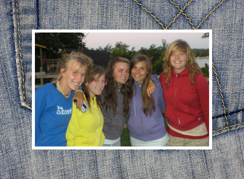 A group photo of five teens. Erinn is in the middle; she has long, wavy brown hair and is wearing a grey TNA hoodie over a white t-shirt