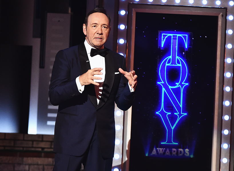 kevin spacey wearing a tux holding his hands up