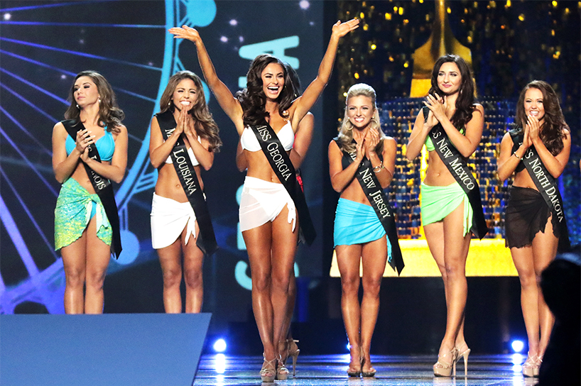 Contestants from the Miss America swimsuit competition stand on stage and clap. They are wearing swimsuits.