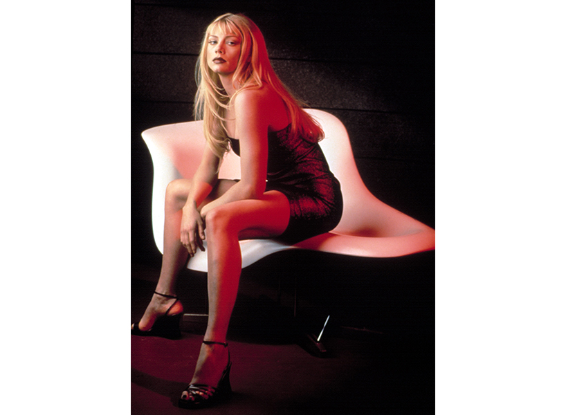 A photo of La Femme Nikita star Peta Wilson sitting on a white chair in a black dress (Photo: La Femme Nikita star Peta Wilson, Everett Collection)