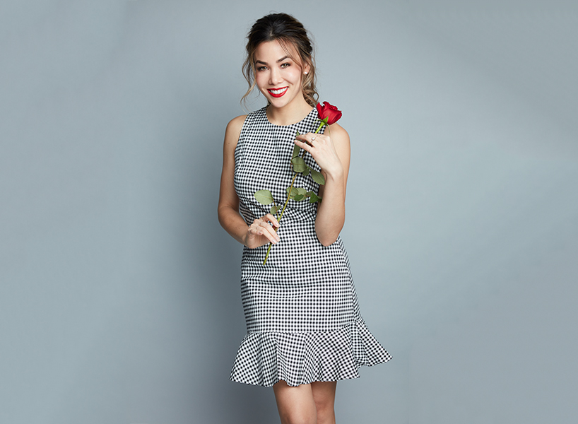 Sharleen Joynt in a black and white gingham dress holding a rose