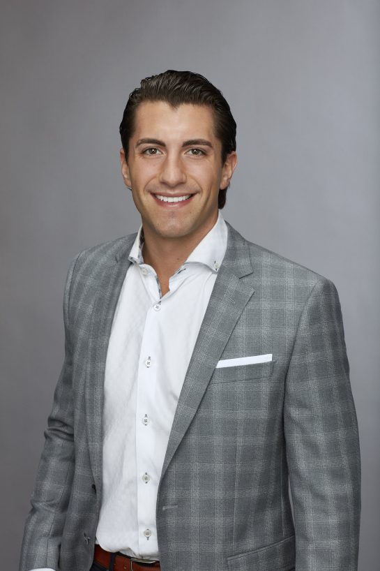 A photo of Bachelorette season 14 contestant Jason Tartick in a grey stio and qhite shirt