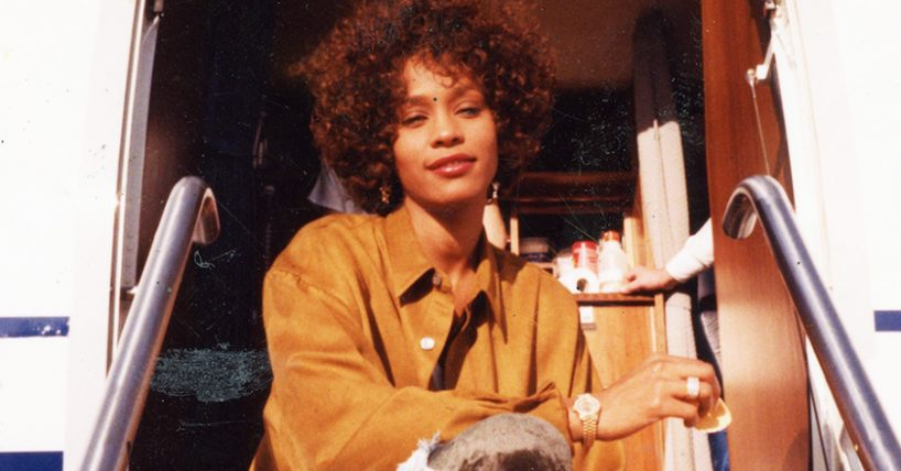 A family photo of Whitney Houston in a brown suede jacket