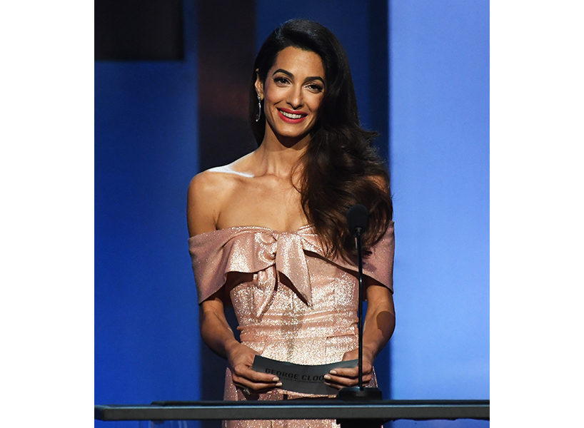 Amal Clooney stands at the podium, smiling and wearing a pastel pink off-the-shoulder sparkly dress