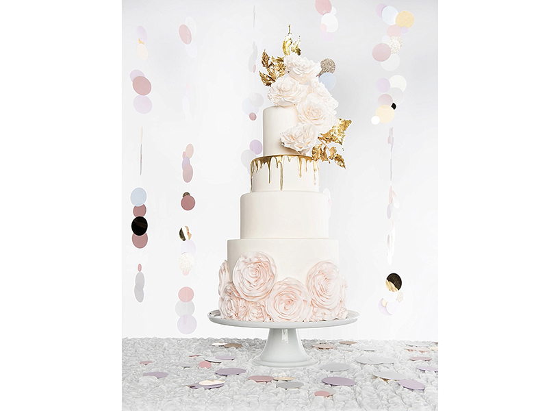 Wedding cakes Calgary: A white cake with gold accents and roses from Calgary's Whippt Desserts, one of the best wedding cakes in Canada