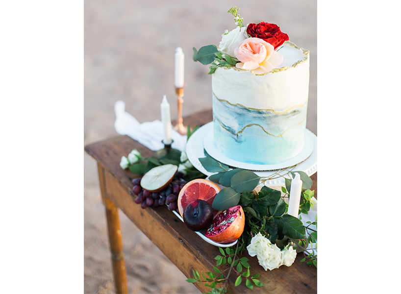 A marble cake with roses and blue accents at Charlottetown's Butter, one of the best wedding cakes in Canada
