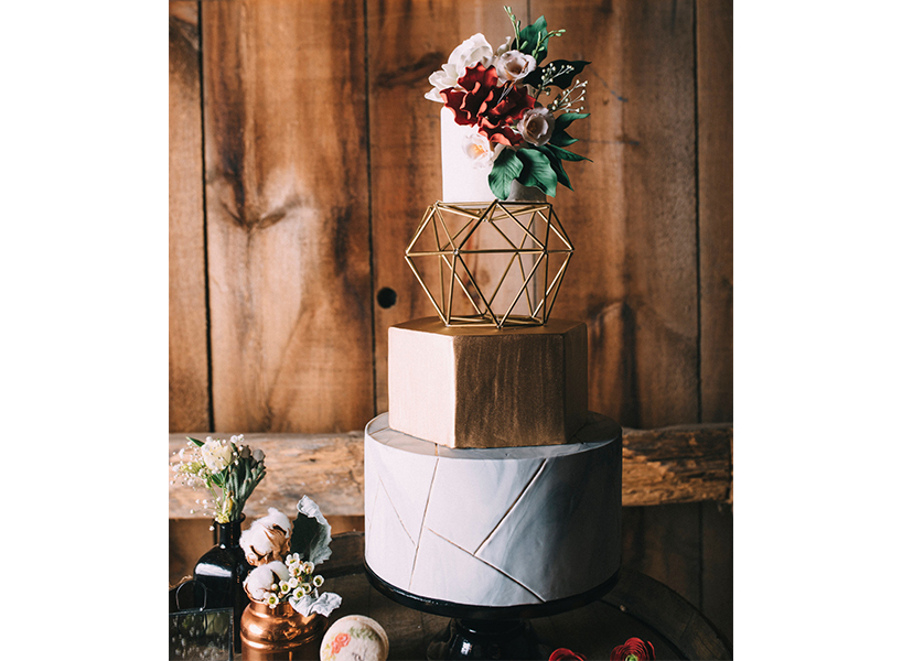 Wedding cakes Montreal: A geometric cake with flowers and a metal piece from Montreal's Sweet Savour by Felicia, one of the best wedding cakes in Canada