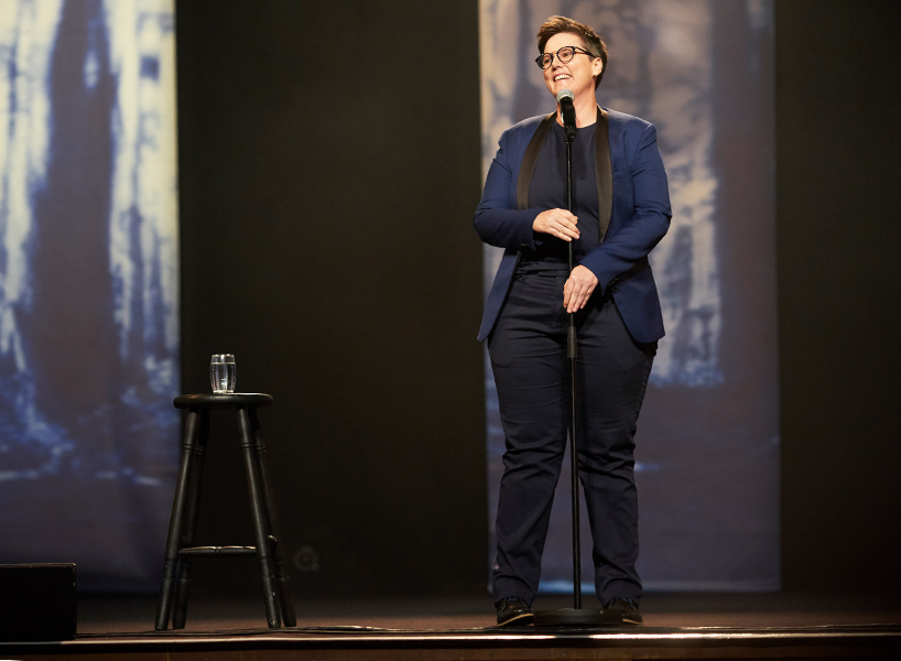 Hannah Gadsby in Netflix's Nanette standup special, wearing a blue suit jacket with black lapels and tilting her head back and smiling at the mic