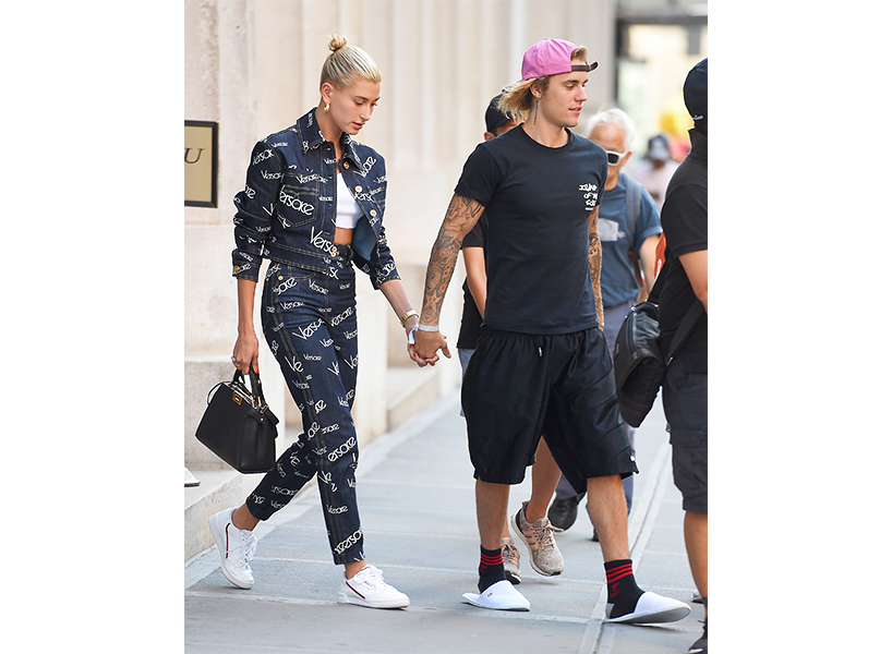 A photo of Justin Bieber in a black t-shirt, shorts and slides with Hailey Baldwin