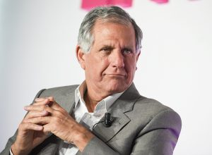 CBS executive Les Moonves sitting on stage in a grey suit and white collared dress shirt with his hands clasped in front of him