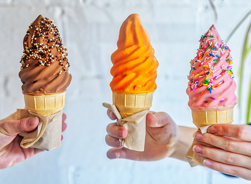 Three hands holding dipped soft serve cones, one brown, one orange and one pink with sprinkles