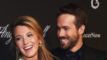 Blake Lively wearing a yellow dress and smiling and Ryan Reynolds wearing an all-black ensemble smiling at her