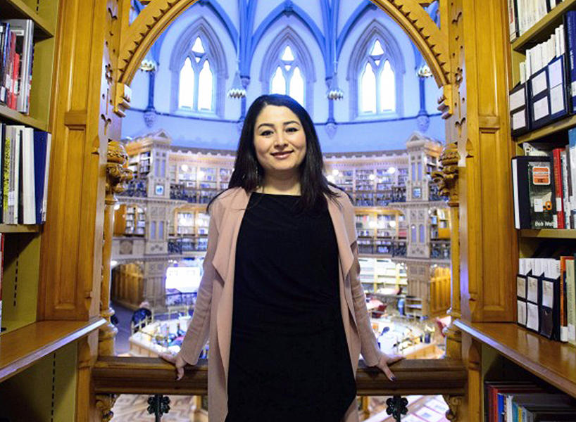 Maryam Monsef stands in a library
