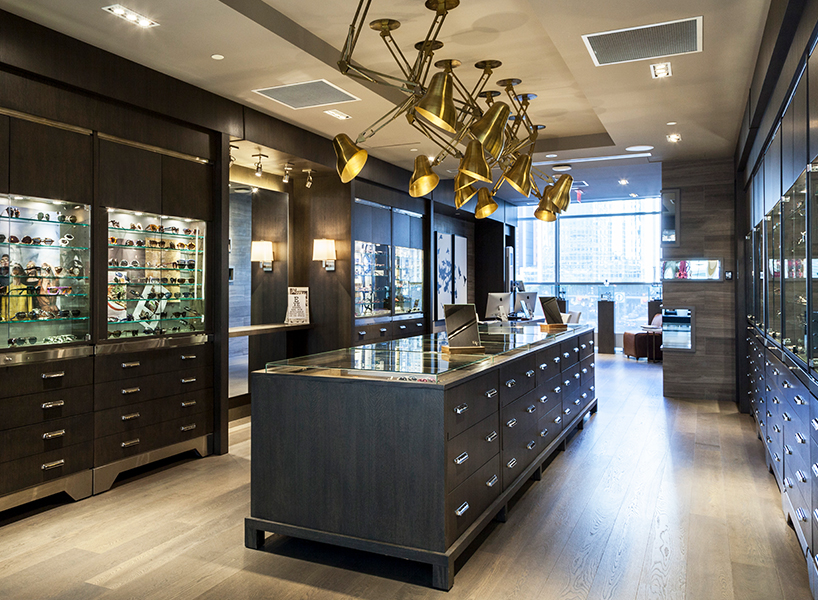 A sunglasses shop with grey wood, gold light fixtures and glass cases of sunglasses