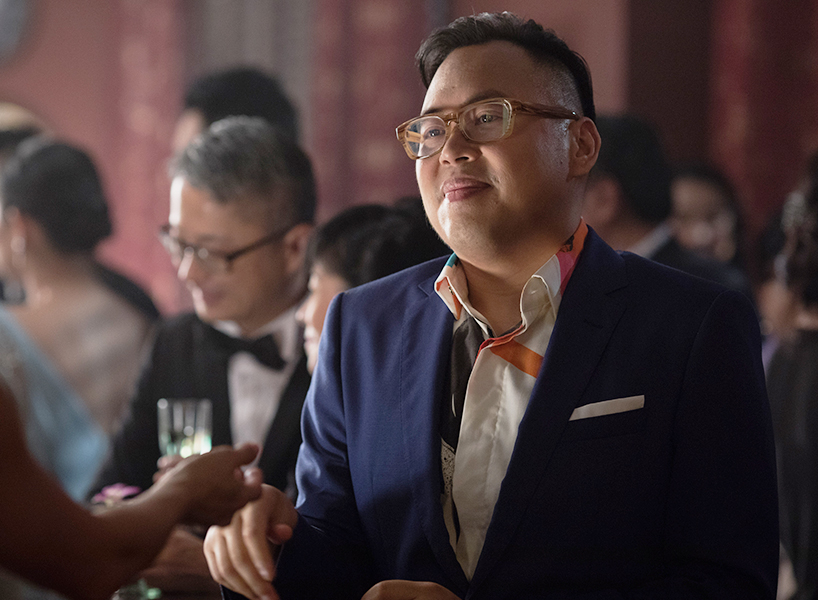 Nico Santos wearing a blue suit and designer shirt underneath giving a smug grin in a party scene from Crazy Rich Asians