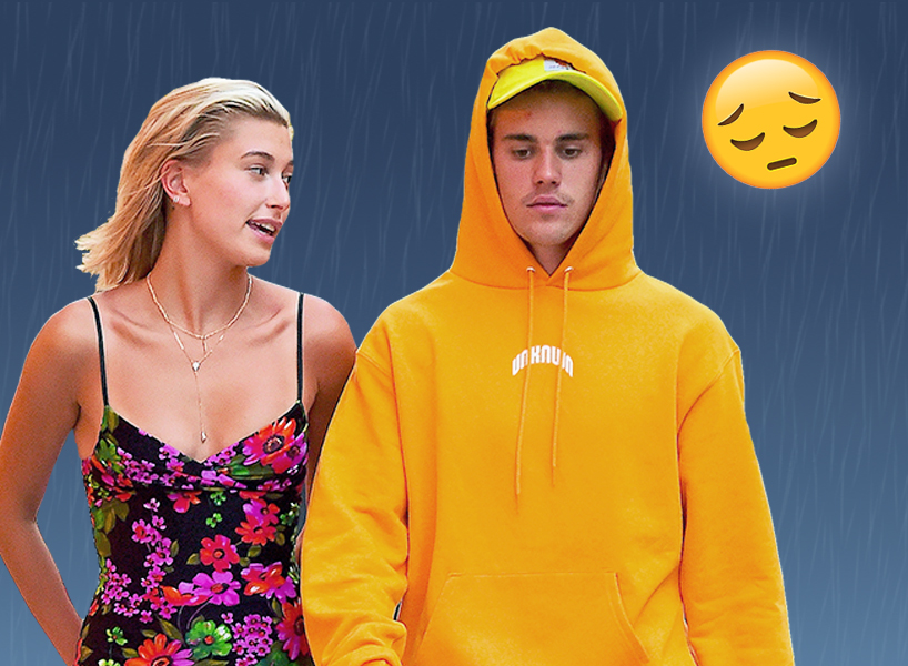 Justin Bieber, wearing an orange hoodie and blue baggy shorts, walks with fiancee Hailey Baldwin in a purple red and green floral dress