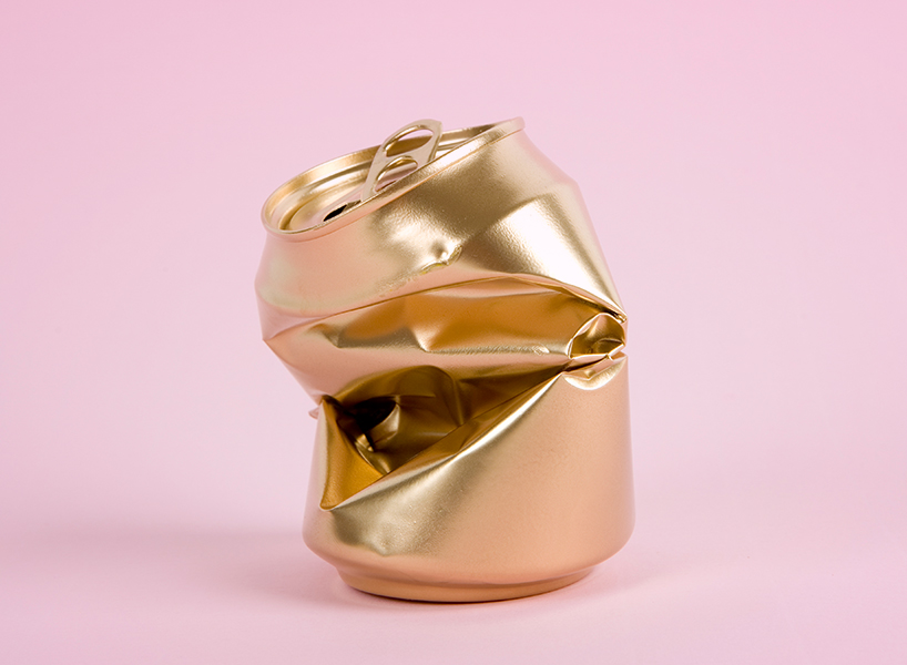 Buck-a-beer: A photo of a crushed gold can on a pink backdrop-inline