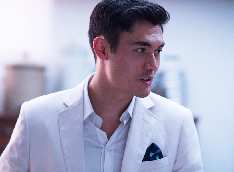 Henry Golding wearing a white suit with white dresshirt and patterned pocket square