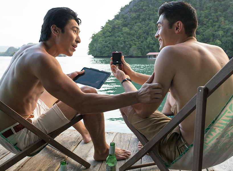Nick and Colin from Crazy Rich Asians sit in chairs on a dock in swim trunks while Nick shows his friend an engagement ring