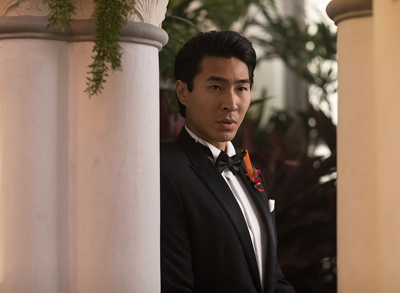 Colin Khoo from Crazy. Rich Asians looks past a pillar wearing a suit