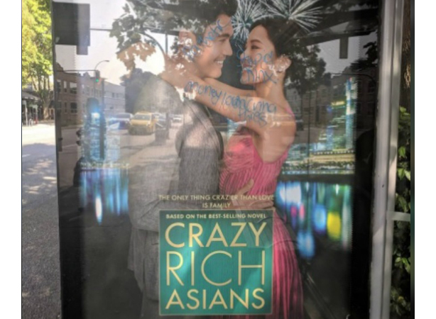 A Twitter photo of a Crazy Rich Asians poster with racist graffiti on it