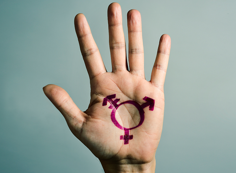 A hand with a transgender logo drawn in purple paint