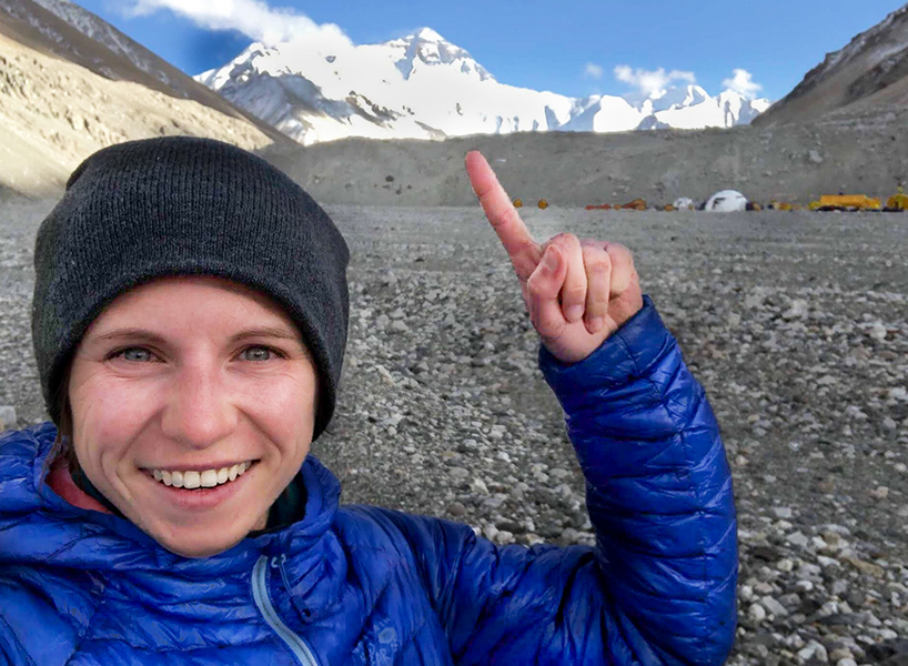 Illina Frankiv smiling and pointing to Mount Everest