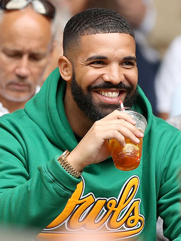 Drake, wearing a green sweatshirt, sips a drink and smiles at Wimbledon