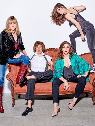 the cast of the baroness von sketch show sits on a pink couch
