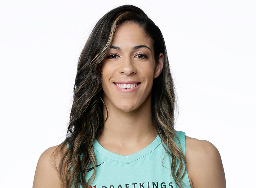 kia nurse smiles on white background wearing turquoise basketball jersey