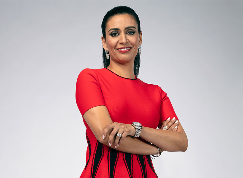 manjit minhas wears red dress and poses with arms crossed