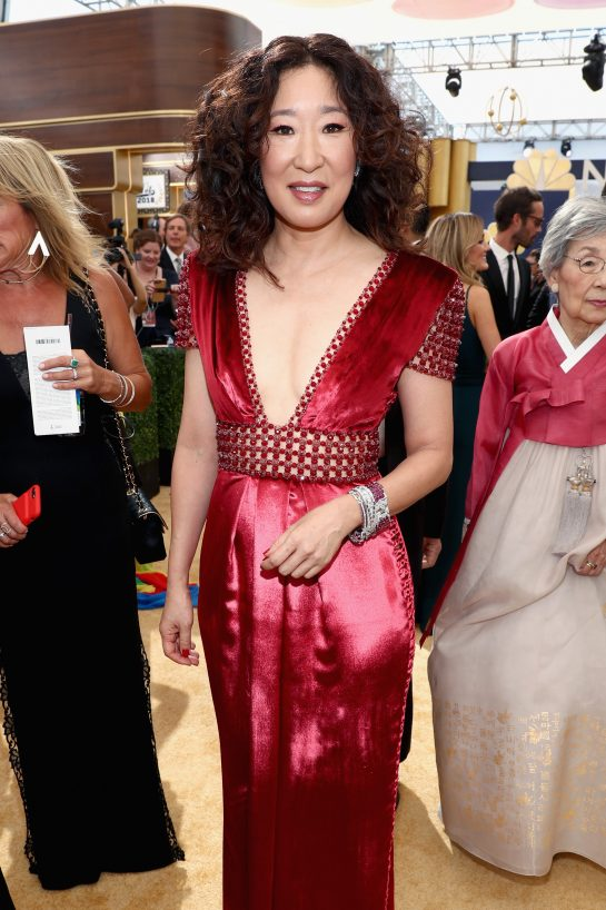 Sandra Oh in a garnet satin deep-v down