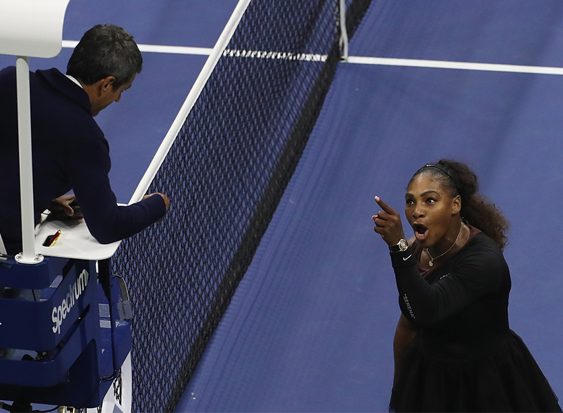 Serena Williams, standing on the blue court at the US Open, points up and argues with umpire Carlos Ramos, who is sitting in a high white chair (Photo: Jaime Lawson/Getty)