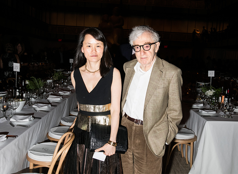 Director Woody Allen wears a beige suit and stands beside his wife Soon-Yi Previn, wearing a black and gold dress at an event