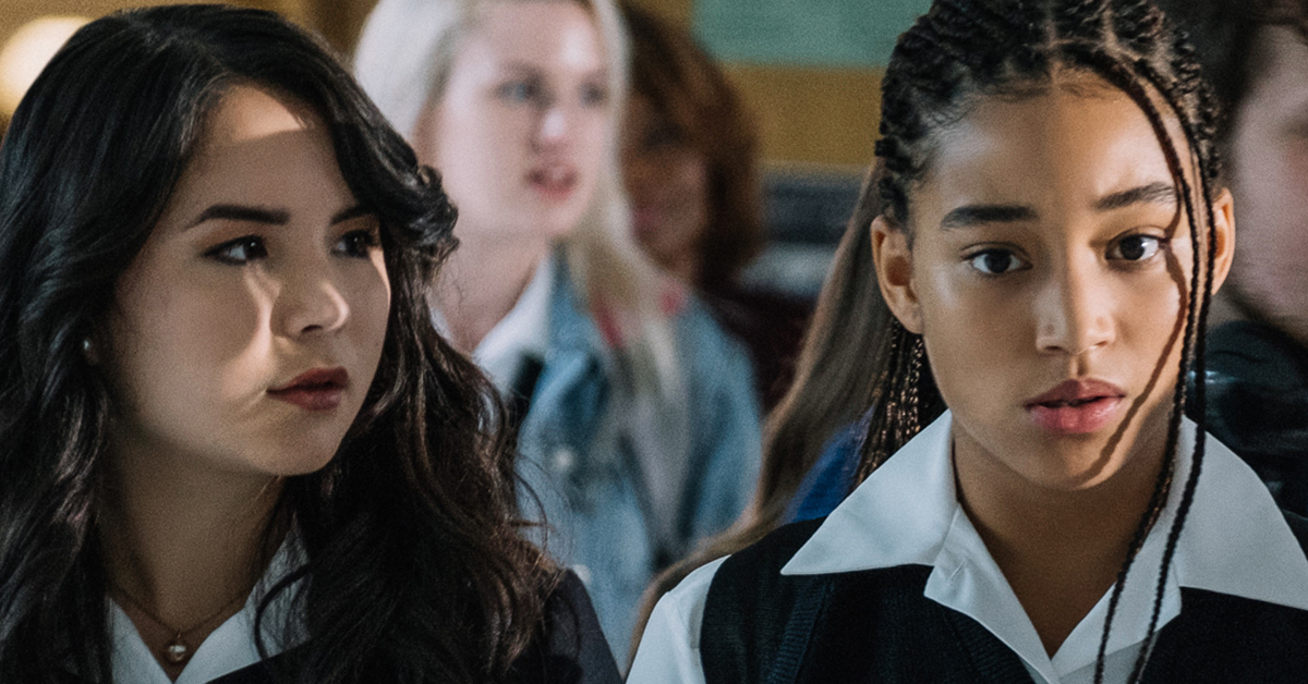 Amandla Stenberg in a screenshot from The Hate U Give, her hair is braided and in a ponytail and she looks serious. She is wearing a school uniform and walking alongside her friend