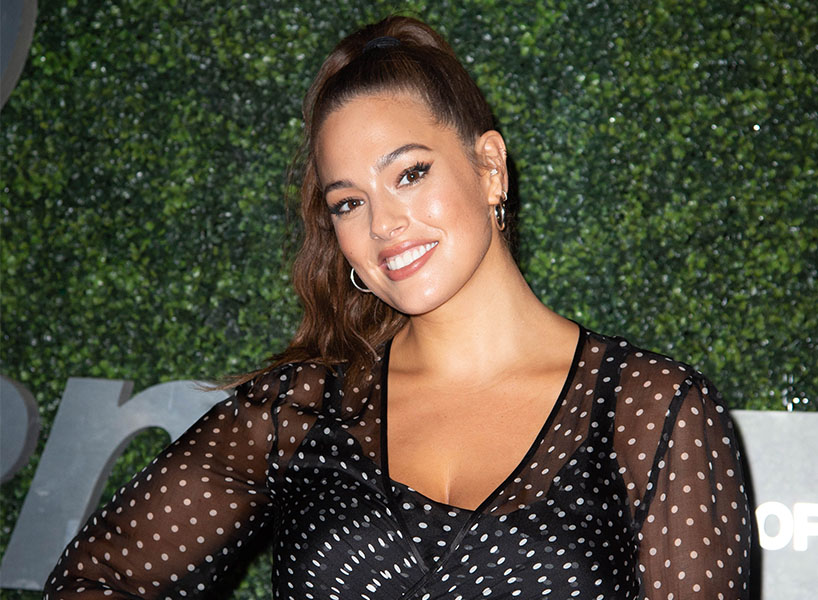 celebrities on body hair: Ashley Graham wears gold hoops, high ponytail, and black sheer polka dotted outfit